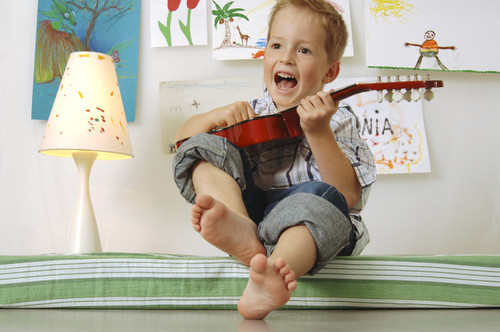 Boy playing with a guitar